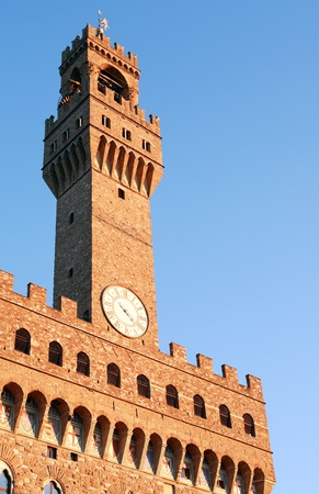 vechio: Closeup of Palazzo Vecchio tower against blue sky. Florence, Italy