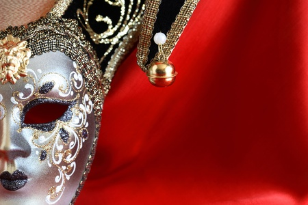 Closeup of classical venetian mask on red silk background with free space for text photo