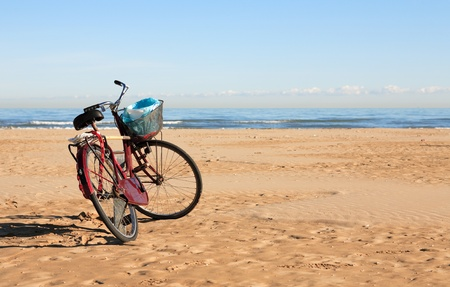 garbage can: Bicycle with garbage can standing on beach against blue sky