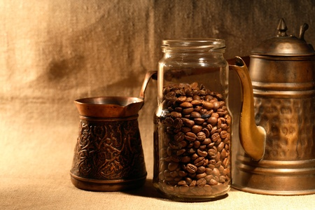 coffeepot: Glass jar with coffee beans near old copper coffeepot on canvas background