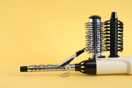 Hairdressing set with various accessories on yellow background
