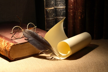 Vintage library still life. Old books, spectacles,scroll, quill pen