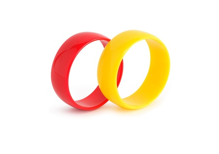 costume jewelry: Costume Jewelry. Red and yellow plastic bangles on white background.