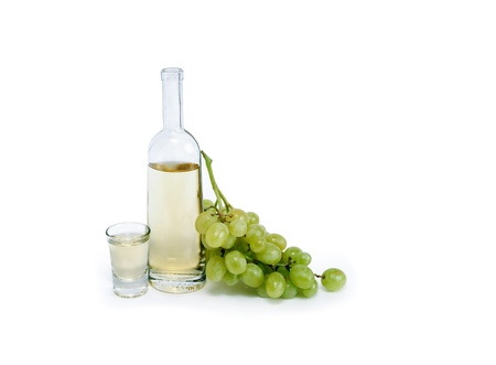 grappa: Open bottle of grappa near wineglass and bunch of grapes on white background.