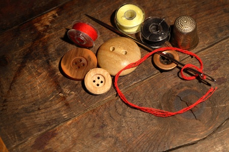Sewing concept.Closeup of few buttons and needle with thread on wooden background photo