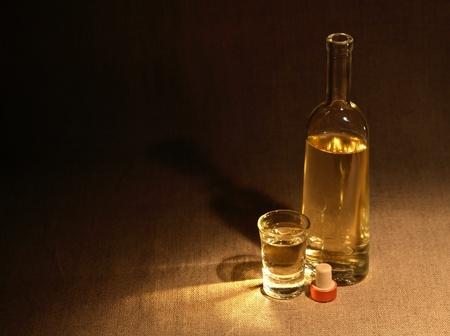 moonshine: Open bottle of wine or vodka near wineglass on canvas surface under beam of light Stock Photo