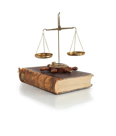legislation: Legislation concept. Old brass weight scale standing on ancient book on white background