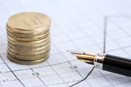 Business concept. Closeup of fountain pen near stack of coins on graph paper with diagram photo