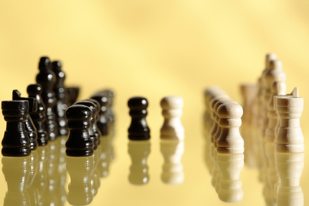chessman: Chessman set in a row on yellow background with reflection Stock Photo