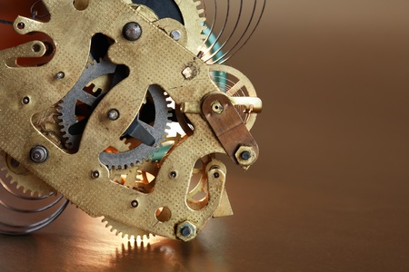 Closeup of old clock mechanism on brown background with free space for text photo
