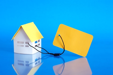 Paper house attached to yellow blank price tag on blue background photo