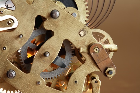 Closeup of old clock mechanism on brown background photo
