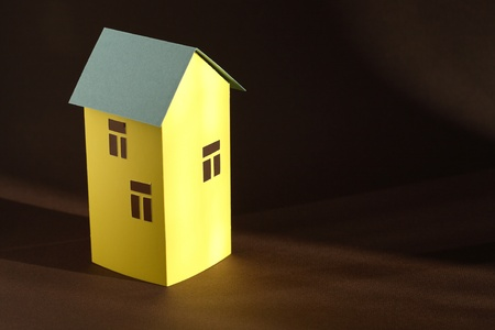 Nice yellow paper house with green roof on dark background photo