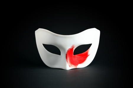 Art concept. White mask with red spot of paint on black background photo