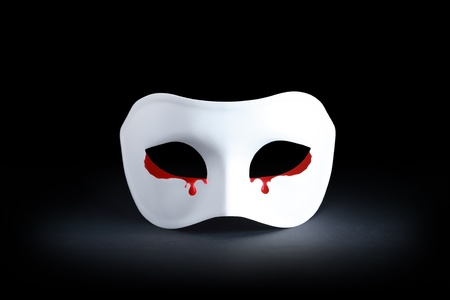 Suffering concept. White mask with bloody tears on black background photo