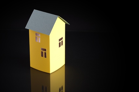 Nice yellow paper house with green roof on dark background with free space for text photo