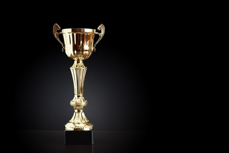 Gold trophy on black background with free space for text
