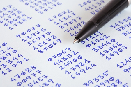 cryptogram: Closeup of bollpoint pen on paper with columns of written numbers