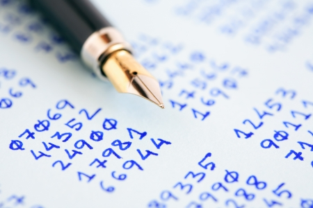 cryptogram: Closeup of fountain pen on paper with columns of written numbers