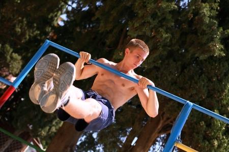 rekstok: Jonge tiener sterke atleet doet pull-up op de horizontale balk