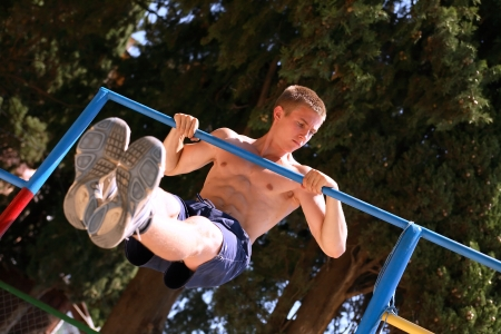 muscularity: Young strong teenage athlete doing pull-up on horizontal bar Stock Photo