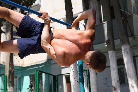rekstok: Jonge tiener sterke atleet doet lichaamsbeweging op de horizontale balk
