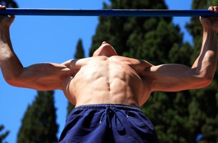 rekstok: Close-up van de jonge tiener sterke atleet doet pull-up op de horizontale balk Stockfoto