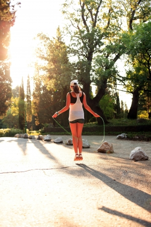 Beauty svelte teenage girl jumping rope in morning park