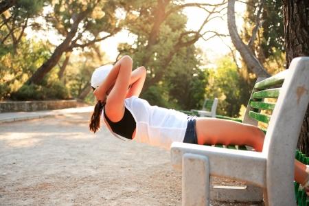 haciendo ejercicio: Belleza joven haciendo ejercicio en banco en el parque por la ma�ana Foto de archivo