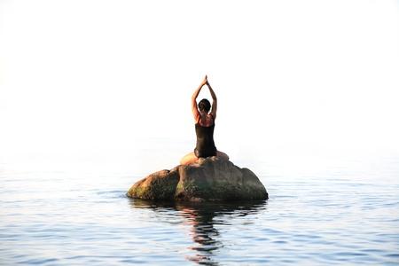 海の石でヨガの練習をやっているしなやかな大人の女性