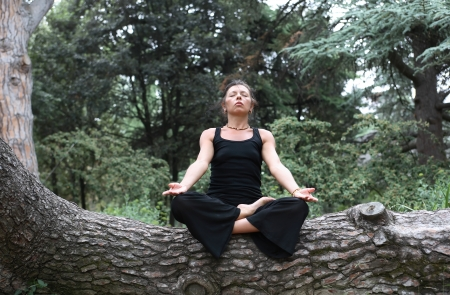 svelte: Svelte adult woman in black sitting in lotus position on forest background