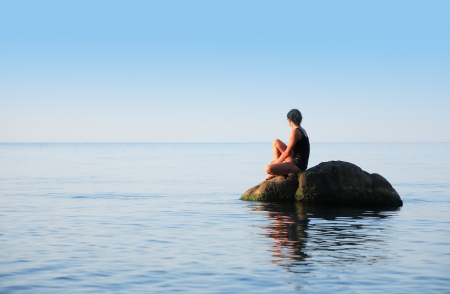 svelte: Svelte adult woman sitting on big stone in the sea and looking to horizon