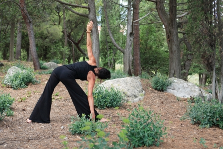 svelte: Svelte adult woman in black doing yoga in forest between stones and woods