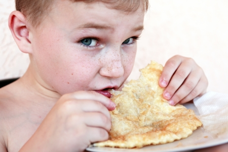 meat pie: Closeup portrait of little boy eating meat pie named cheburek