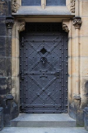 Ancient building with gloomy black metal door photo