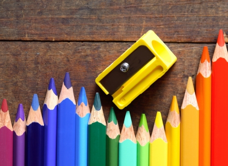 Closeup of variegated crayons in a row near pencil sharpener on wooden background photo