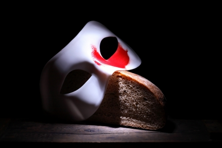 circuses: Roman Empire concept. White mask with red spot lying on bread on black background Stock Photo