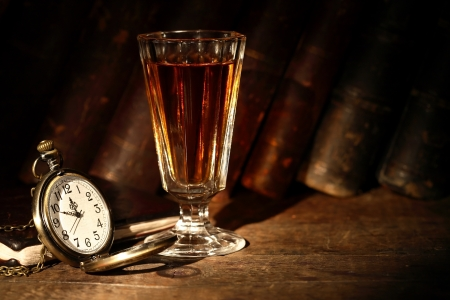 Vintage small wineglass with alcohol near open pocket watch on background with old books photo