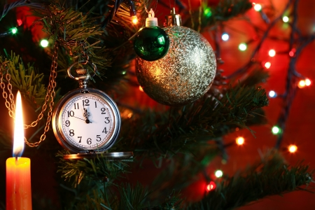 Vintage pocket watch hanging on Christmas tree near lighting candle photo