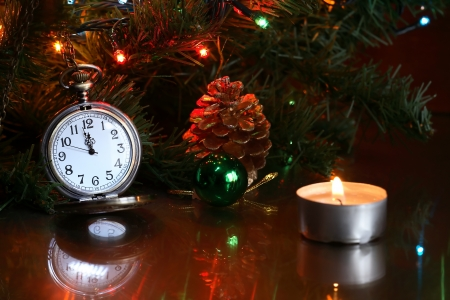 Vintage pocket watch near Christmas tree and lighting candle photo
