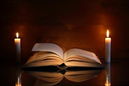 2 つの照明蝋燭近く開いた古い本のヴィンテージの静物 写真素材
