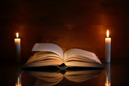 Vintage still life with open old book near two lighting candles