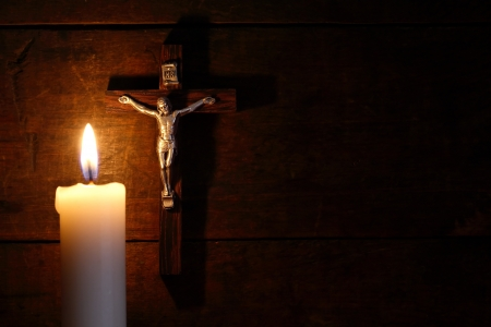 easter candle: Small crucifix hanging on old wooden wall near lighting candle