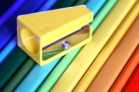 Closeup of yellow sharpener on color pencils surfase photo