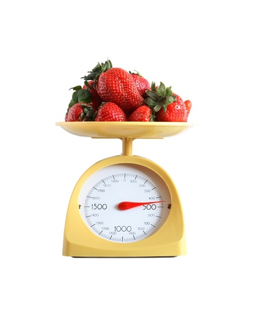 measuring instrument: Heap of strawberry fruits lying on nice yellow kitchen scale. Isolated on white  Stock Photo
