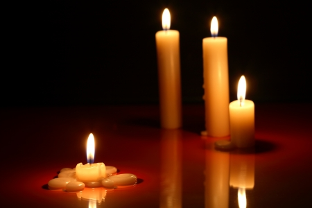 Wenige Anzünden von Kerzen auf dunklem Hintergrund mit Reflexion