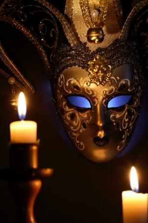 Anzünden von Kerzen gegen schöne klassische venezianische Maske auf dunklem Hintergrund Standard-Bild