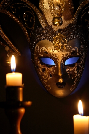 theatre masks: Lighting candles against beautiful classical venetian mask on dark background