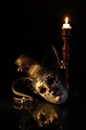 Beautiful classical venetian mask lying near lighting candle on dark background