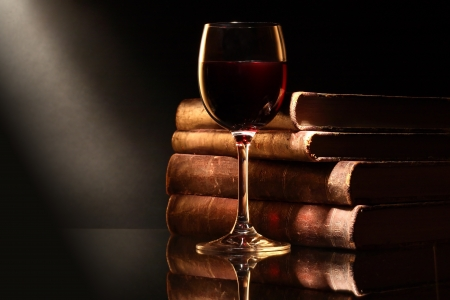 Elegant goblet of red dry wine near old books on dark background
